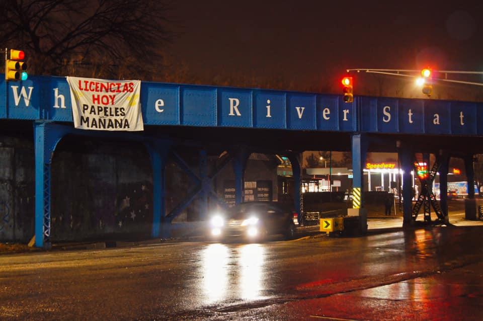 "A banner reading ""Licencias hoy, papeles mañana"" is draped over an overpass"