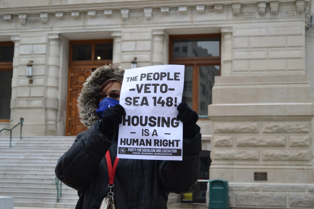 """Doris Jones of the PSL holds up a banner that reads"""" The people VETO SEA 148"""""""