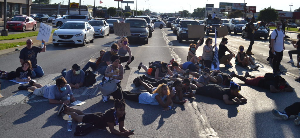 Protesters lay down on the street, blocking traffic as drivers lean out of their cars in support.