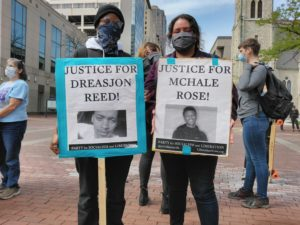 """Two individuals hold banners, one reading """"Justice for Dreasjon Reed"""" (left) and the other reading """"Justice for McHale Rose"""" (right)"""